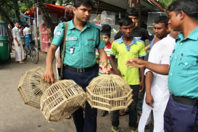 Police officer confiscating illegally-caputured birds (photo courtesy of Animesh Ghose and GES)