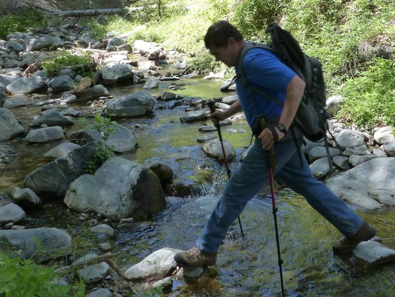 Ted Daehnke former zookeeper crossing stream in the southern california mountains
